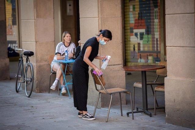 Una cambrera neteja les cadires d'una terrassa. Barcelona, Catalunya (Espanya), 26 de maig del 2020.