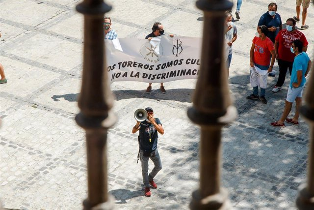"""Un hombre con un megáfono perteneciente al sector taurino protesta junto a otras personas a las puertas del Ayuntamiento de Toledo a la llegada de la ministra de Trabajo, Yolanda Díaz, a quien han recibido con pitos y con gritos de """"dimisión"""""""