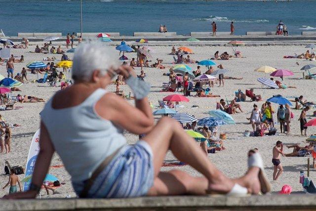 Una persona sentada frente a la playa en A Mariña