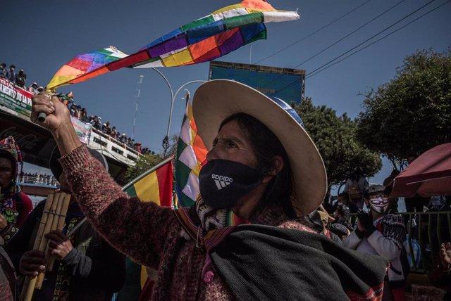 Una mujer con una bandera wiphala y mascarilla durante la movilización para protestar contra la postergación de las elecciones generales de Bolivia.