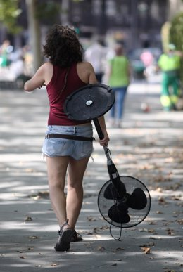 Una mujer pasea por una calle con un ventilador en la mano