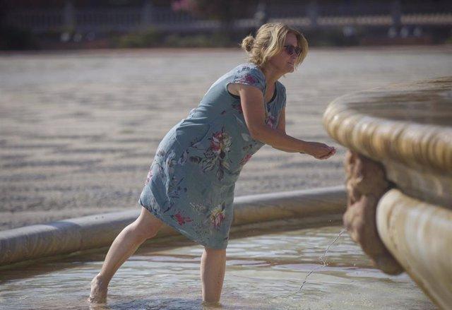 Una mujer se refresca en la fuente de la Plaza de España de Sevilla