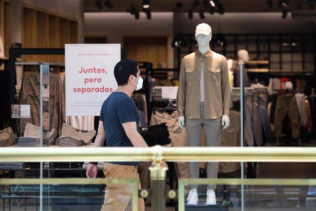 Un hombre pasa delante de una tienda, Archivo.