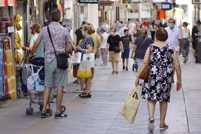 Personas en una calle comercial. Imagen de archivo.