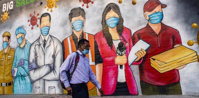 Mural de personas con mascarillas en Nueva Delhi