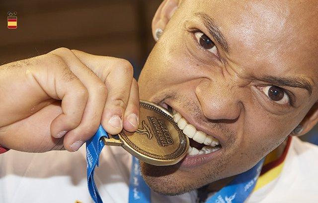 El gimnasta español de origen dominicano Ray Zapata muerde su medalla en los Juegos Mediterráneos de Almería 2018