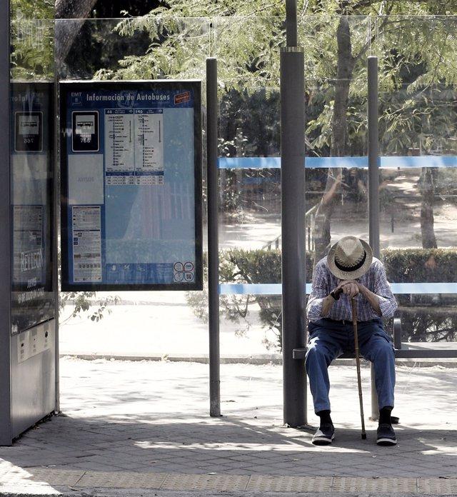 Un pensionista espera el autobús en la marquesina de una parada de Madrid.