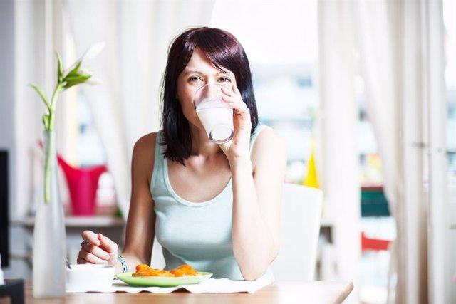 Mujer bebiendo leche en el desayuno.