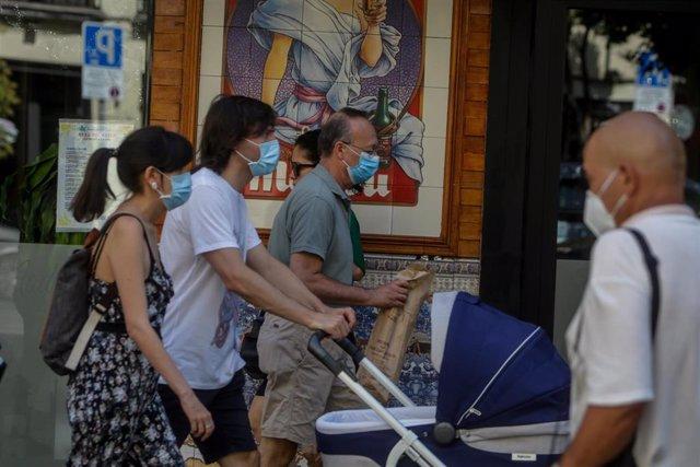 Transeúntes pasean por las calles de la capital, que junto a Canarias, es la única comunidad autónoma de España donde sigue sin ser obligatorio usar la mascarilla aún sin distancia interpersonal. En Madrid, (España), a 19 de julio de 2020.