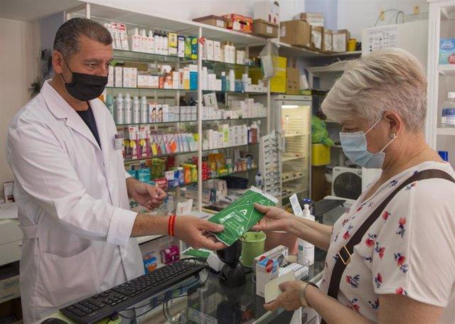 Una mujer adquiere las mascarillas gratuitas que la Junta de Andalucía en una imagen de archivo.