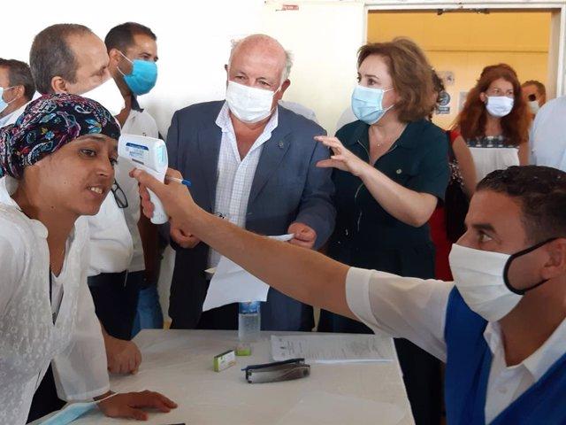 El consejero de Salud, Jesús Aguirre, juntao a la delegada del Gobierno, Sandra García, en la despedida a las últimas temporeras marroquíes que han partido este marte desde Huelva.