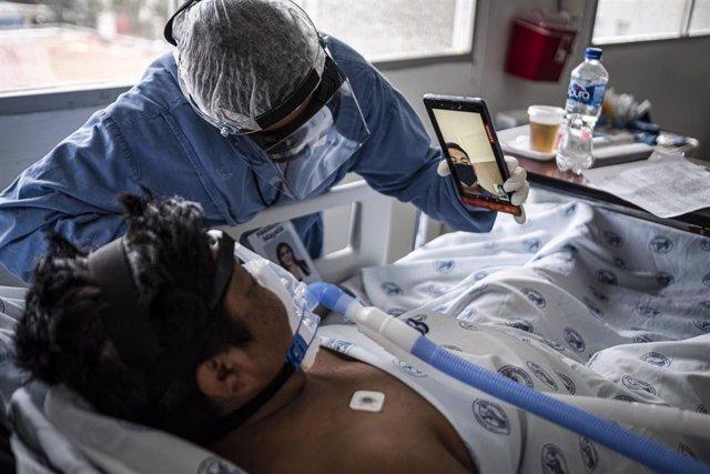 Un médico sostiene un móvil para que un paciente de COVID-19 pueda hacer una videollamada en Chihuahua, México.