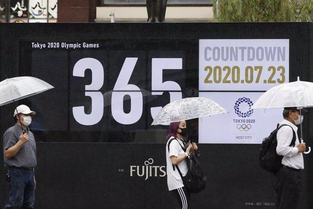 Gent amb mascareta en un passeig amb el compte enrere per als Jocs Olímpics de Tòquio