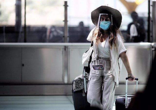 Una pasajera caminando con maleta por un pasillo de la terminar T4 del Aeropuerto Adolfo Suárez Madrid Barajas, en Madrid (España), a 24 de julio de 2020.