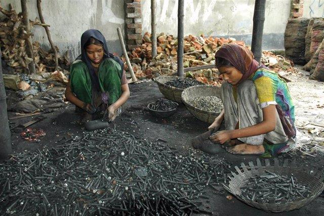 Unas niñas de 12 y 18 años trabajando con material tóxico en una calle de Bangladesh