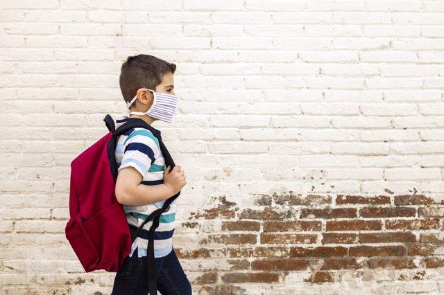 Niño con mascarilla andando al colegio.