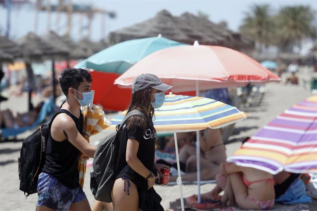Dos personas con mascarillas mientras pasan entre sombrillas en la playa
