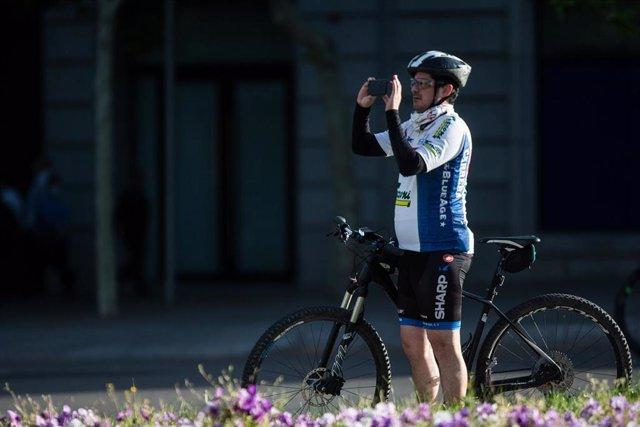 Un ciclista realiza una foto con el teléfono móvil
