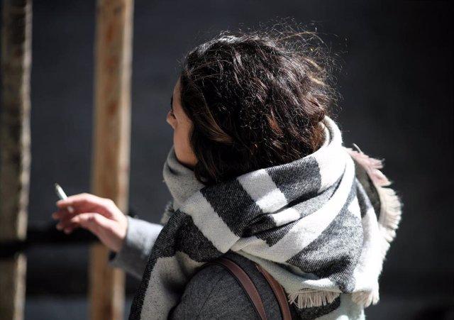 Una mujer abrigada con bufanda y abrigo, fumando durnate un día de viento por Madrid (España), a 8 de noviembre de 2019.
