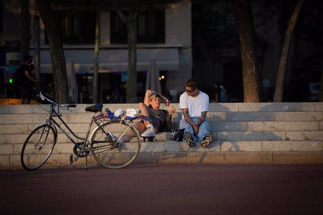 Dos jóvenes junto a una bicicleta en Barcelona, Catalunya (España), a 28 de julio de 2020.