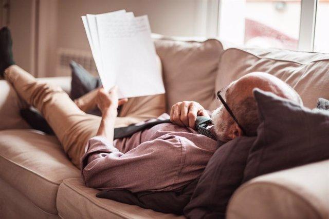 Hombre mayor tumbado en un sofá leyendo.