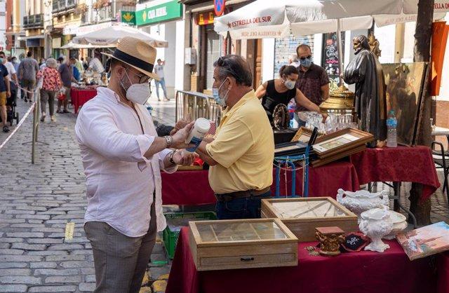 Un cliente se lava las manos con gel hidroalcohólico  en el 'Mercadillo de el Jueves' de la calle Feria. Sevilla a 09 de julio del 2020