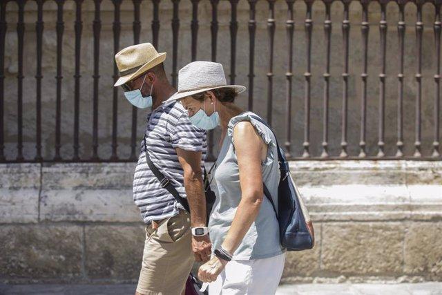 Dos personas caminan con mascarilla y sombrero durante la ola de calor africano que ha llegado este jueves a España. En Sevilla (Andalucía, España), a 30 de julio de 2020.