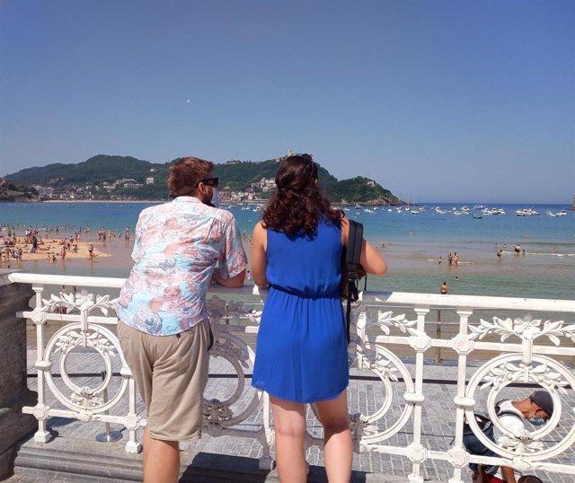 Una pareja contempla las vistas de la Playa de la Concha en San Sebastián el día en el que las temperaturas máximas podrían alcanzar los 37 grados en la zona costera del País Vasco, en San Sebastián, Guipúzcoa, Euskadi (España) a 30 de julio de 2020. La D