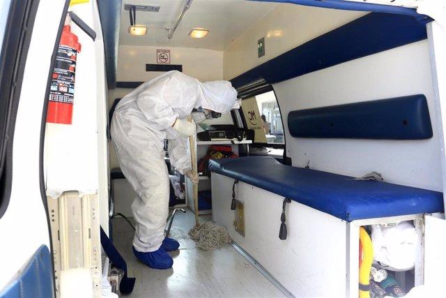 Un trabajador sanitario limpia una ambulancia en León (México) durante la pandemia de coronavirus