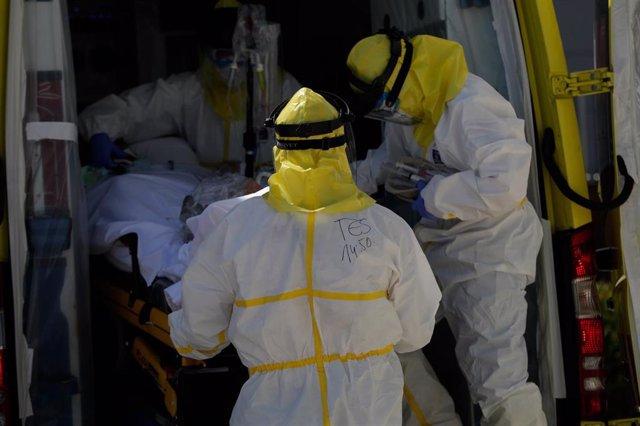 Varios sanitarios trasladan a un paciente desde el interior de la unidad móvil.