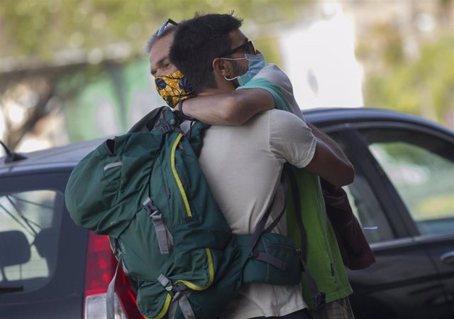 Dos personas se abrazan este viernes en Sevilla capital.