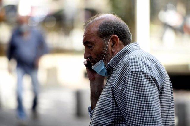 Un hombre con mascarilla habla por teléfono en la calle, en Madrid (España) a 30 de julio de 2020.