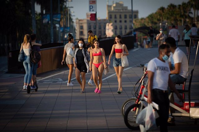 Varias jóvenes caminan en bañador por Barcelona, Catalunya (España), a 28 de julio de 2020.