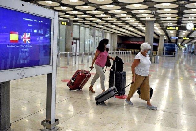 Dos pasajeras con maletas en la terminal T1 del Aeropuerto de Madrid-Barajas Adolfo Suárez, en Madrid (España).