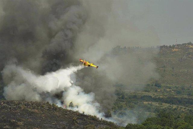 Un avión apaga fuegos de la UME sobrevuela y vierte agua sobre el incendio de Cualedro (Ourense).
