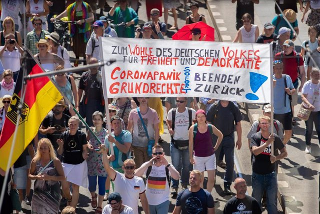 01 August 2020, Berlin: People take part in a demonstration at Friedrichstrasse street held against the restrictive measures imposed by the government to curb the spreading of coronavirus. Photo: Christoph Soeder/dpa