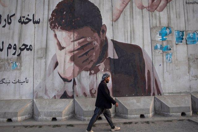 Un ciudadano pasea ante un mural por Kabul