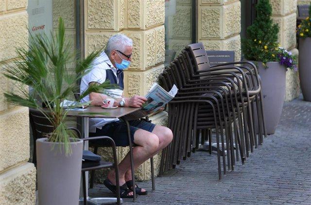 Un hombre con mascarilla lee un periódico durante la pandemia de coronavirus en Italia
