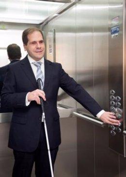Una persona con ceguera acciona el botón de un ascensor