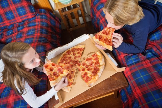 Children Eating Takeout Pizza in Their Bedroom