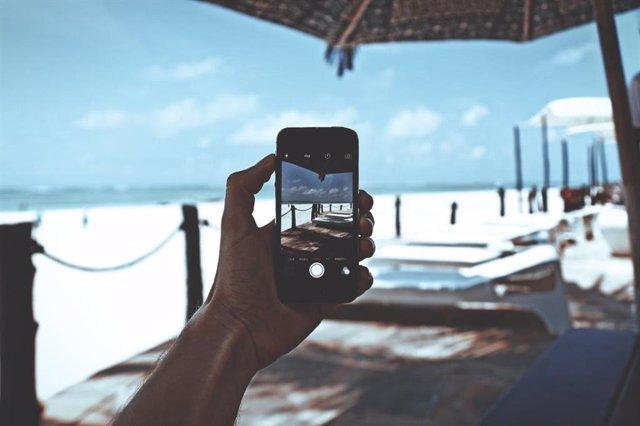 Una persona utiliza un teléfono móvil en la playa