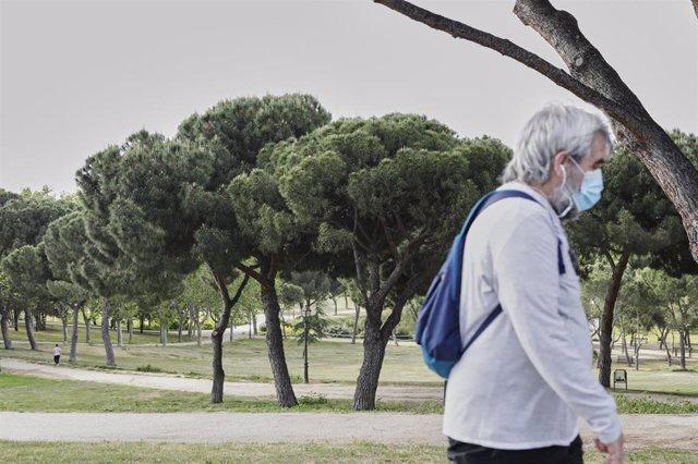 Un hombre con mascarilla pasea protegido por el parque de San Isidro,