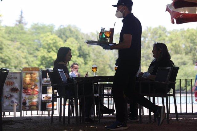 Un camarero protegido con mascarilla atiende a una mesa de una de las terrazas abiertas en el Parque de El Retiro durante el cuarto día de la Fase 1 en Madrid