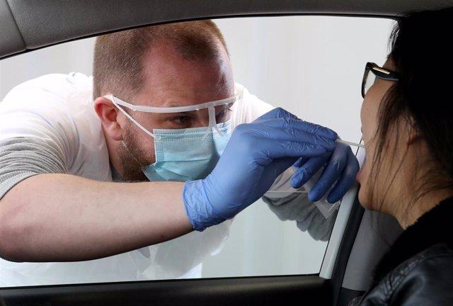 Un sanitario realiza una prueba diagnóstica de la COVID-19 a una mujer en Edimburgo, Escocia.