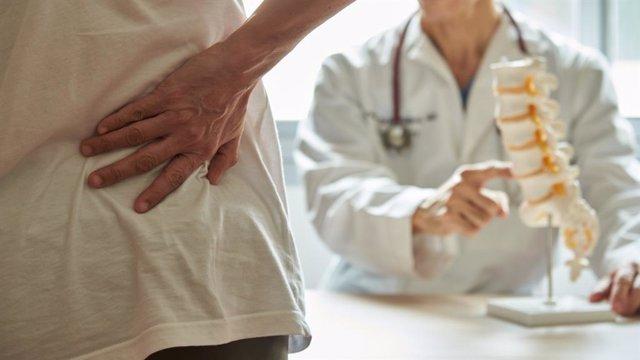 Un médico que explica anatomía lumbar al paciente con dolor de espalda.