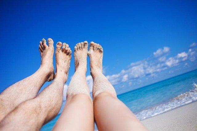Piernas de una pareja en la playa.