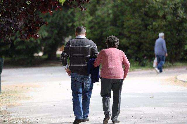 Un hombre acompaña a una mujer de edad avanzada a pasear.