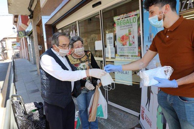 Reparto a dos clienes de mascarillas a la puerta de un Supermercado en Algete (Madrid)