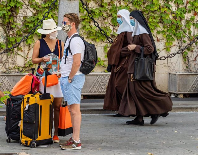 Unos turistas esperan el autobús mientras una pareja de monjas de la Orden de Santa Ángela de la Cruz  pasan por detrás con mascarillas el día que se ha anunciado la caída de un 98,9% de turistas extranjeros en Andalucía. Sevilla a 3 de agosto del 2020