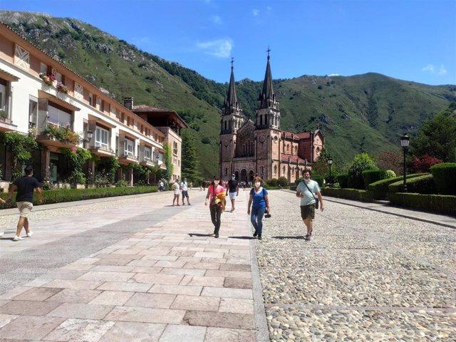 Gente paseando por la recientemente acondicionada explanada del Santuario de Covadonga con mascarillas.